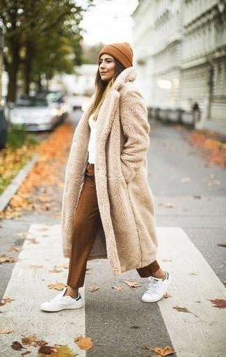 Equípate un abrigo de piel beige junto a un gorro para que te veas verdaderamente magnífica. ¿Quieres elegir un zapato informal? Haz tenis de cuero blancos tu calzado para el día.