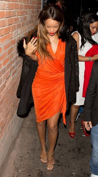 Cómo combinar: abrigo de piel negro, vestido cruzado naranja, sandalias de tacón de cuero doradas