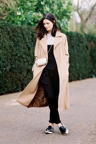 Para seguir las tendencias usa un abrigo beige y un peto vaquero negro. Haz este look más informal con zapatillas slip-on de cuero negras.