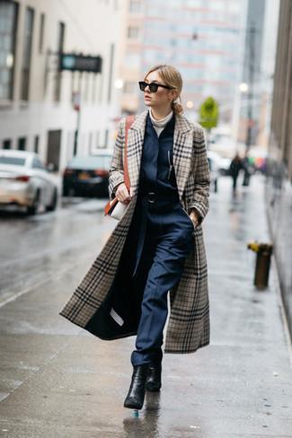 Cómo combinar: abrigo de tartán en beige, jersey de cuello alto sin mangas blanco, mono azul marino, botines de cuero negros