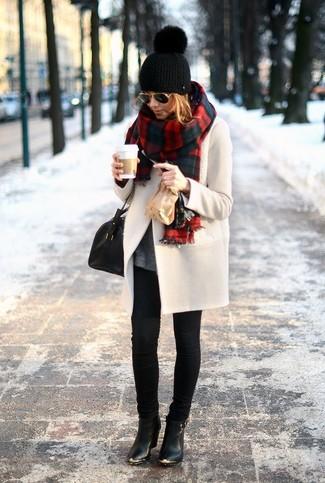 Ponte un abrigo beige y unos vaqueros pitillo negros para una vestimenta cómoda que queda muy bien junta. Este atuendo se complementa perfectamente con botines de cuero negros.