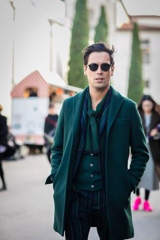 Cómo combinar: abrigo largo verde oscuro, blazer de rayas verticales en azul marino y verde, cárdigan verde oscuro, pantalón de vestir de rayas verticales en azul marino y verde