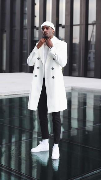 Cómo combinar: abrigo largo blanco, jersey de cuello alto blanco, pantalón chino negro, tenis de cuero blancos