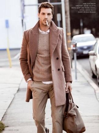 Destaca entre otros civiles elegantes con un abrigo largo y un pantalón chino marrón claro.