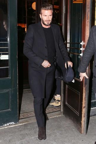 Look de David Beckham: Abrigo largo negro, Jersey con cuello circular negro, Pantalón de vestir negro, Botines chelsea de ante en marrón oscuro