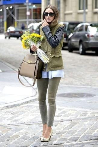 Cómo combinar: anorak verde oliva, blusa de manga larga blanca, vaqueros pitillo verde oliva, zapatos de tacón de cuero dorados