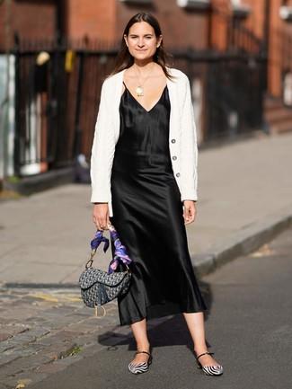 Cómo combinar: bolso de hombre de lona estampado gris, bailarinas de cuero en blanco y negro, vestido camisola de satén negro, cárdigan de punto blanco