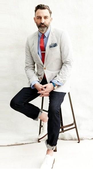 Cómo combinar: blazer en beige, camisa de manga larga celeste, vaqueros negros, zapatos derby de cuero blancos