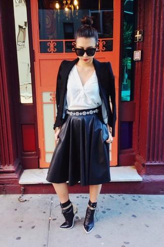 Cómo combinar: blazer negro, camisa de vestir de rayas verticales blanca, falda campana de cuero negra, botines de cuero con print de serpiente negros