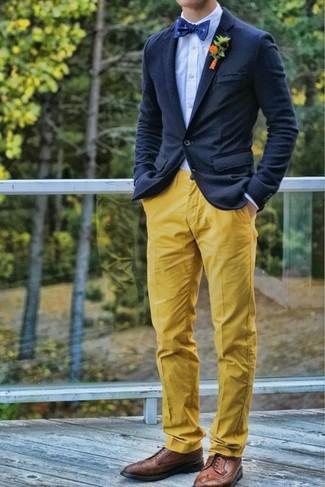 Cómo combinar: blazer de lana azul marino, camisa de vestir celeste, pantalón chino amarillo, zapatos brogue de cuero marrónes