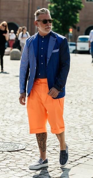 Cómo combinar: blazer de rayas verticales azul marino, camisa de vestir azul marino, pantalones cortos naranjas, zapatillas slip-on de lona grises