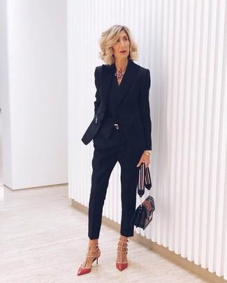 Cómo combinar: blazer negro, camisa de vestir negra, pantalones pitillo negros, zapatos de tacón de cuero con tachuelas rojos