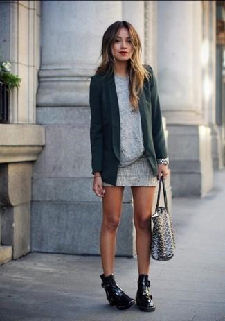 Un blazer verde oscuro y una minifalda son el combo perfecto para llamar la atención por una buena razón. Botines de cuero con recorte negros añaden la elegancia necesaria ya que, de otra forma, es un look simple.