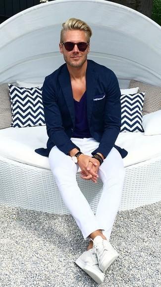 Cómo combinar: blazer azul marino, camiseta con cuello en v azul marino, pantalón chino blanco, tenis de cuero blancos