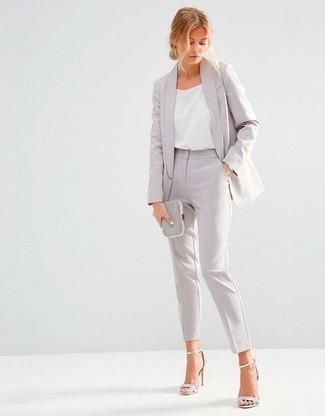 Cómo combinar: blazer gris, camiseta sin manga de seda blanca, pantalón de vestir gris, sandalias de tacón de cuero plateadas