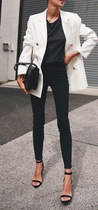 Cómo combinar: blazer cruzado blanco, camiseta con cuello circular negra, vaqueros pitillo negros, sandalias de tacón de ante negras
