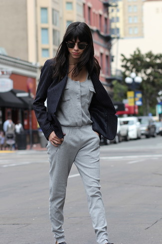 Para crear una apariencia para un almuerzo con amigos en el fin de semana usa un blazer de rayas verticales negro y un mono gris. Para el calzado ve por el camino informal con zapatillas slip-on de cuero negras.