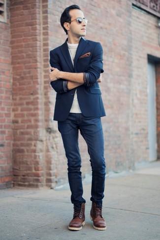 Un jersey con cuello circular gris y unos vaqueros azul marino son prendas que debes tener en tu armario. Luce este conjunto con zapatos brogue de cuero marrónes.