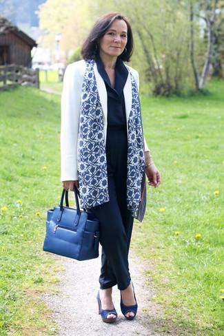 Cómo combinar: blazer blanco, mono azul marino, sandalias de tacón de lona azul marino, bolsa tote de cuero azul marino
