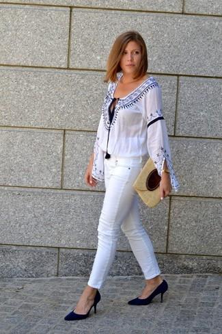 Cómo combinar: blusa campesina bordada en blanco y azul, vaqueros pitillo blancos, zapatos de tacón de ante negros, cartera sobre de paja en beige