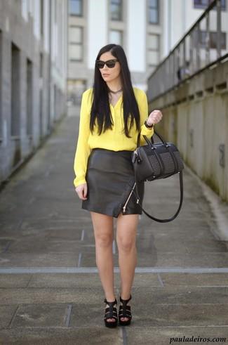 Cómo combinar: blusa de botones de seda amarilla, minifalda de cuero negra, sandalias de tacón de cuero negras, cartera de cuero con adornos negra