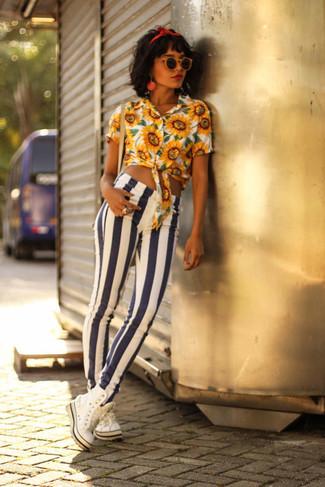 Cómo combinar: blusa de botones con print de flores amarilla, vaqueros pitillo de rayas verticales en blanco y azul marino, zapatillas altas blancas, cinta para la cabeza roja