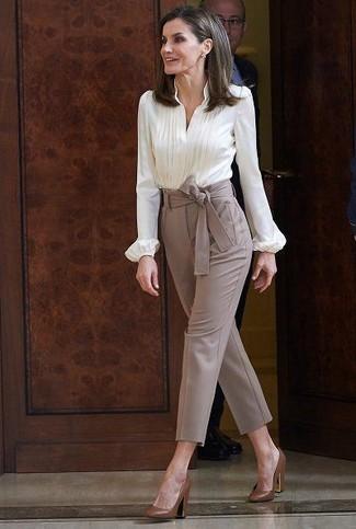 Cómo combinar: blusa de botones blanca, pantalón de pinzas marrón, zapatos de tacón de cuero marrónes