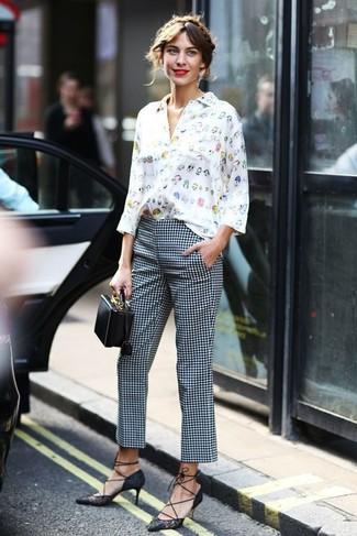 Cómo combinar: blusa de botones estampada blanca, pantalones pitillo a cuadros en blanco y negro, zapatos de tacón de encaje negros, cartera sobre de cuero negra