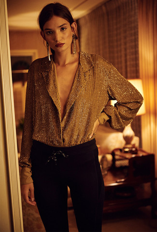 Cómo combinar: blusa de botones dorada, pantalones pitillo negros, pendientes dorados