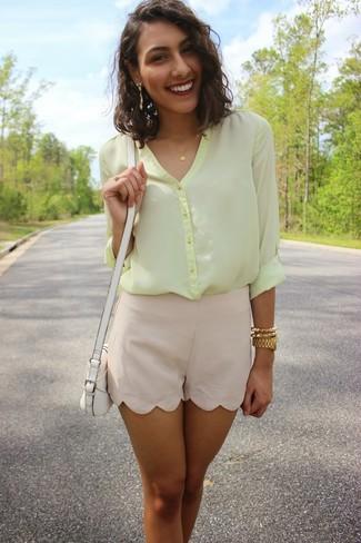 Cómo combinar: blusa de botones de gasa amarilla, pantalones cortos de seda en beige, bolso bandolera de cuero blanco, reloj dorado