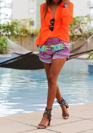 Cómo combinar: blusa de botones naranja, pantalones cortos con print de flores en multicolor, sandalias de tacón de cuero con tachuelas negras, gafas de sol negras