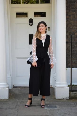 Cómo combinar: blusa de manga larga a lunares blanca, mono negro, sandalias de tacón de ante negras, pendientes negros