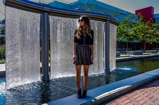 Cómo combinar: blusa de manga larga negra, falda skater dorada, botines de nubuck negros