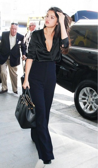 Look de Selena Gomez: Blusa de manga larga de satén negra, Pantalones anchos azul marino, Zapatos de tacón de cuero negros, Bolsa tote de cuero negra