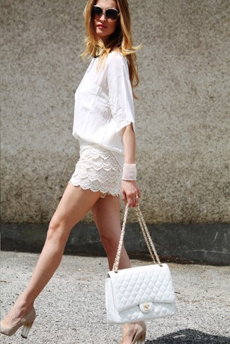 Cómo combinar: blusa de manga larga blanca, pantalones cortos de crochet blancos, zapatos de tacón de ante en beige, bolso de hombre de cuero acolchado blanco