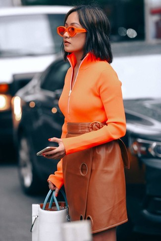 Cómo combinar: gafas de sol naranjas, bolsa tote de cuero blanca, falda lápiz de cuero en tabaco, jersey de cuello alto con cremallera naranja