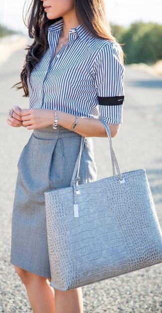 Cómo combinar: pulsera plateada, bolsa tote de cuero con print de serpiente gris, falda lápiz gris, camisa de vestir de rayas verticales en blanco y azul marino