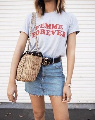 Cómo combinar: correa de cuero negra, bolsa tote de paja marrón claro, minifalda vaquera celeste, camiseta con cuello circular estampada gris