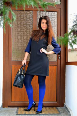 Cómo combinar: medias azules, bolsa tote de cuero con print de serpiente negra, zapatos de tacón de cuero negros, vestido recto en negro y azul
