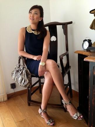 Cómo combinar: reloj dorado, bolsa tote de cuero con print de serpiente gris, sandalias con cuña de cuero con print de serpiente grises, vestido tubo azul marino