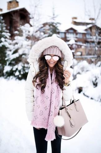 Cómo combinar: gorro de punto rosado, bolsa tote de cuero rosada, vaqueros pitillo negros, abrigo de plumón blanco