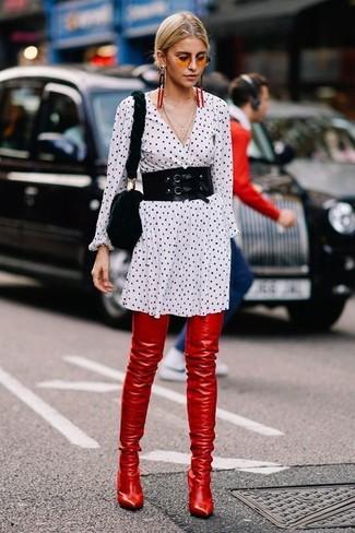 Cómo combinar: cinturón negro, bolso bandolera de pelo negro, botas sobre la rodilla de cuero rojas, vestido camisa a lunares en blanco y negro