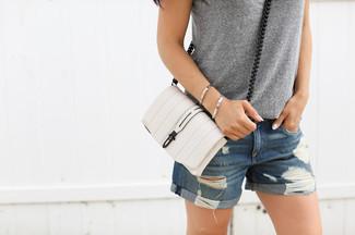 Cómo combinar: bolso bandolera de cuero blanco, pantalones cortos vaqueros desgastados azules, camiseta sin manga gris