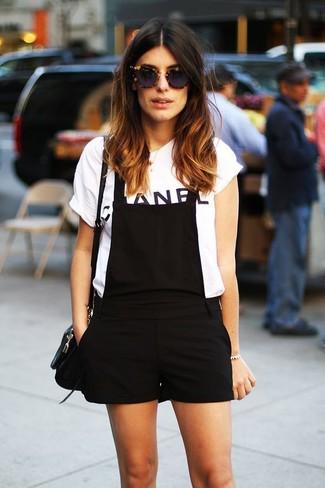 Cómo combinar: bolso bandolera de cuero negro, peto corto negro, camiseta con cuello circular estampada en blanco y negro