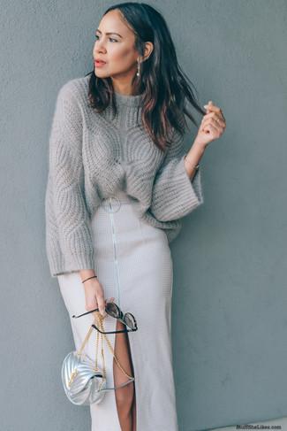 Cómo combinar: bolso bandolera de cuero plateado, falda midi con recorte en beige, jersey oversized de punto gris