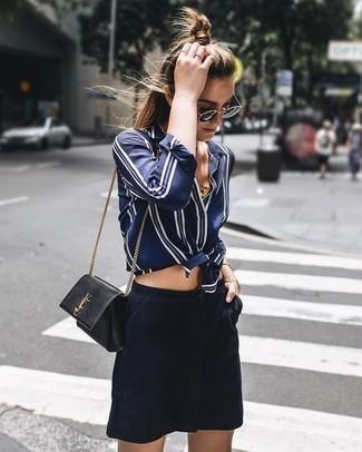 Cómo combinar: gafas de sol en negro y dorado, bolso bandolera de cuero negro, minifalda de ante azul marino, camisa de vestir de seda de rayas verticales en azul marino y blanco