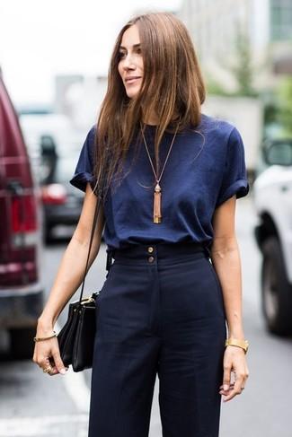 Cómo combinar: colgante dorado, bolso bandolera de cuero negro, pantalones anchos azul marino, camiseta con cuello circular azul marino