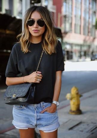 Cómo combinar: gafas de sol en negro y dorado, bolso bandolera de cuero acolchado negro, pantalones cortos vaqueros celestes, camiseta con cuello circular negra