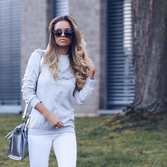 Cómo combinar: gafas de sol marrónes, bolso bandolera de cuero plateado, vaqueros pitillo blancos, jersey con cuello circular gris