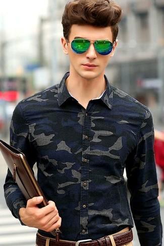Cómo combinar: correa de cuero en marrón oscuro, bolso con cremallera de cuero en marrón oscuro, pantalón chino marrón claro, camisa vaquera de camuflaje azul marino